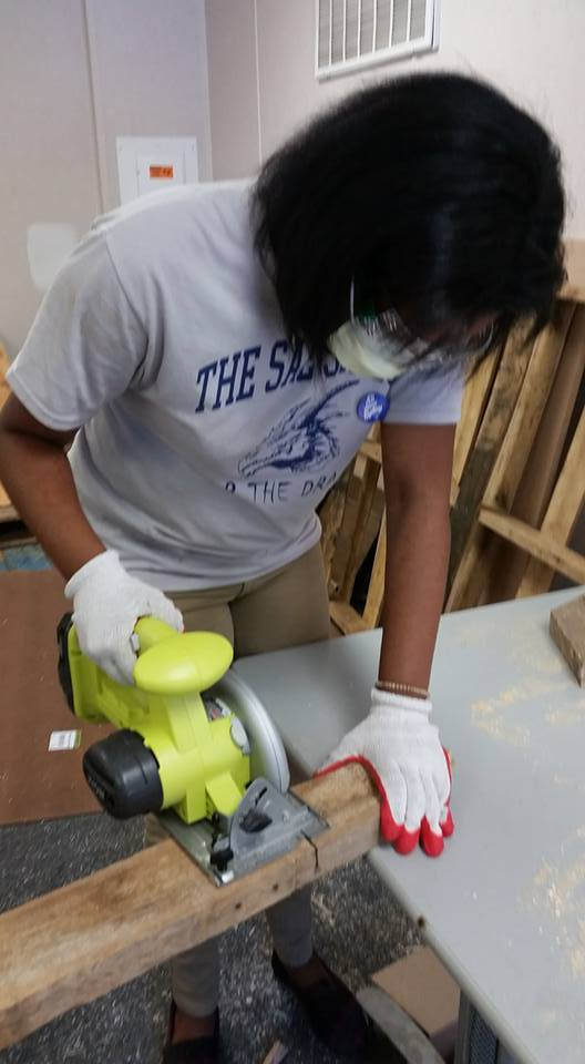 SAE high school student cuts wood for soapbox car.